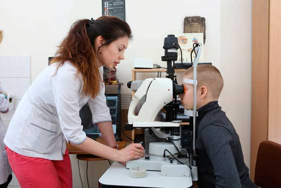 Врач-офтальмолог определяет близорукость у подростка