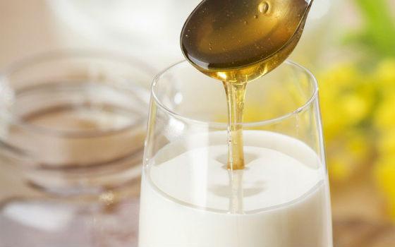 Добавление столовой ложки меда в стакан теплого молока