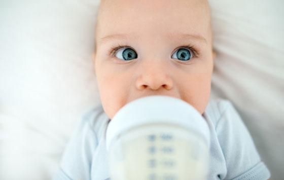 Грудной ребенок пьет молоко из бутылочки