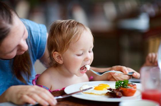 Девочка пробует продукты с тарелки мамы