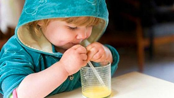 Ребенок пьет сок из яблок через трубочку
